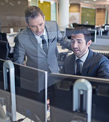 two men collaborating in office on computers